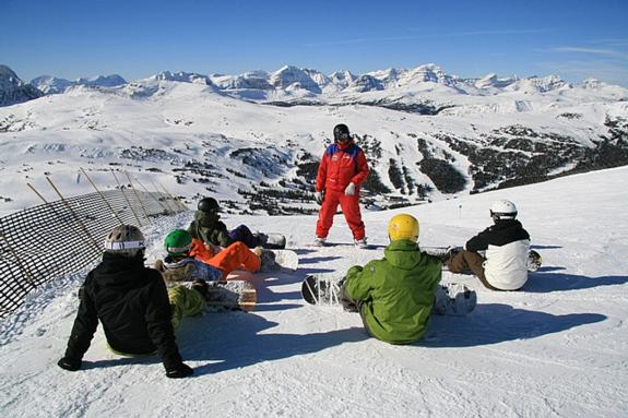 instructor teaching snowboarding