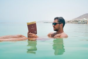passive income - man reading book in water
